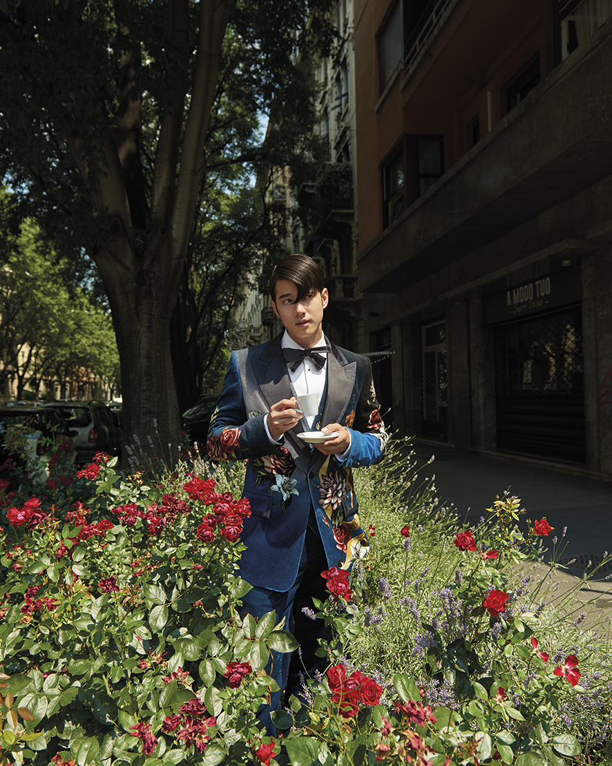 Mario Maurer wears a cotton poplin shirt, velvet jacquard suit, silk bow tie, all by Dolce&Gabbana