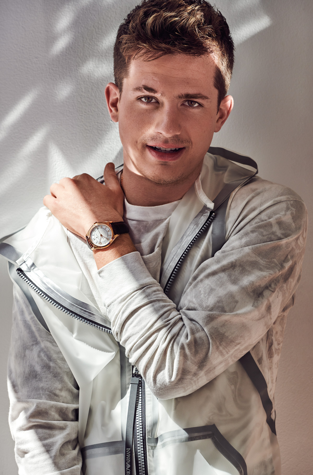 Charlie Puth is wearing the Vacheron Constantin Fiftysix Self-Winding watch in pink gold, a tank top from Emporio Armani, and a sweater from John Elliott