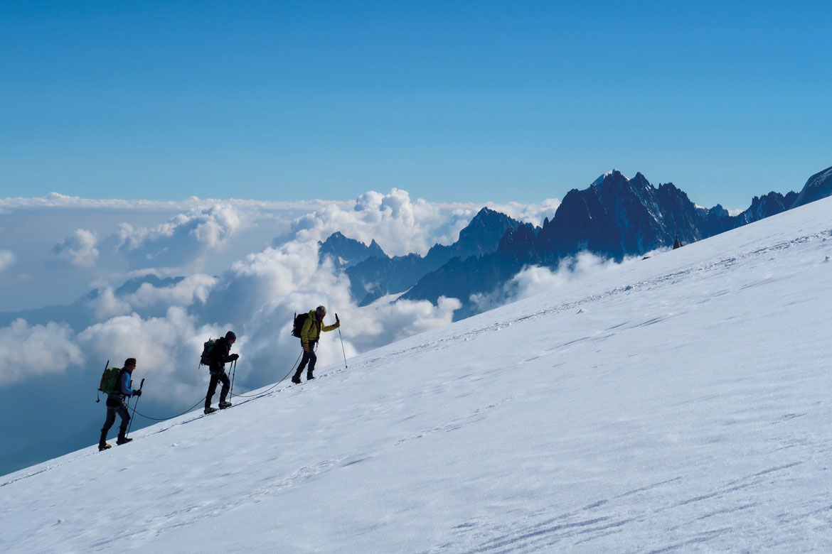 A trio of mountain climbers ascend the slopes