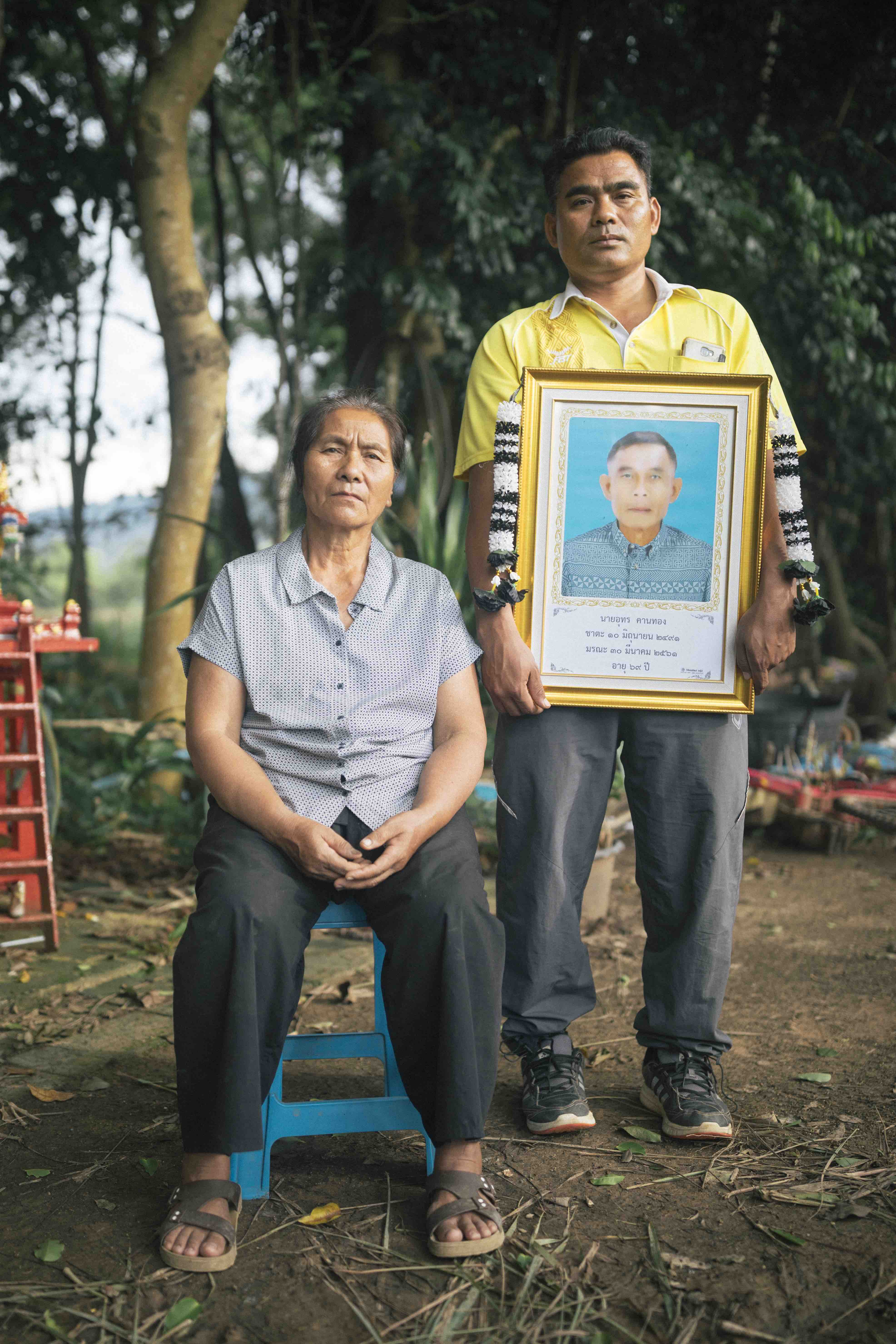 Titipan Khanthong and his mother with a portrait of the late father, Uthorn, who was killed by an elephant in his fields on the border of Khao Yai National Forest.