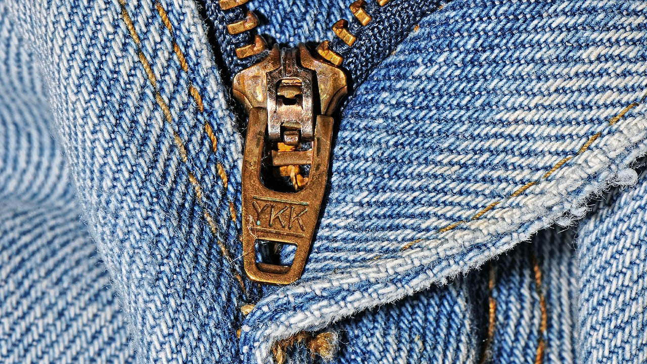 A brass YKK zipper on a jean's fly enclosure