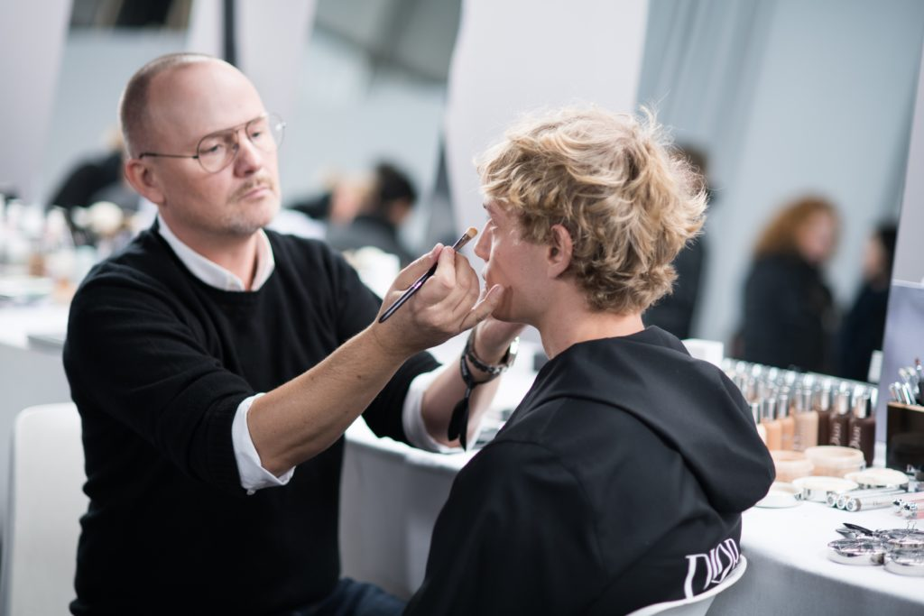 Peter Philips, Dior's makeup maestro, applies makeup on a male model before a show. Photo: Dior Beauty